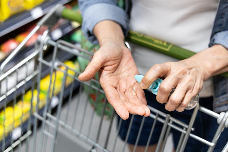 Asian shopper disinfecting hands with sanitizer in supermarket during shopping for groceries. Public shopping cart is high risk virus and bacteria contact point.