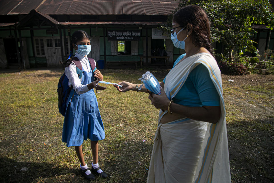 A school principal distributes masks to students as schools in north-eastern Assam state reopen after being closed for months due to the coronavirus pandemic in Gauhati, India, Monday, Nov. 2, 2020. (AP Photo/Anupam Nath)