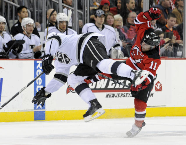 Los Angeles Kings' Dustin Brown, left, and New Jersey Devils' Stephen Gionta collide during the second period of an NHL hockey game Friday, Nov. 15, 2013, in Newark, N.J. (AP Photo/Bill Kostroun)