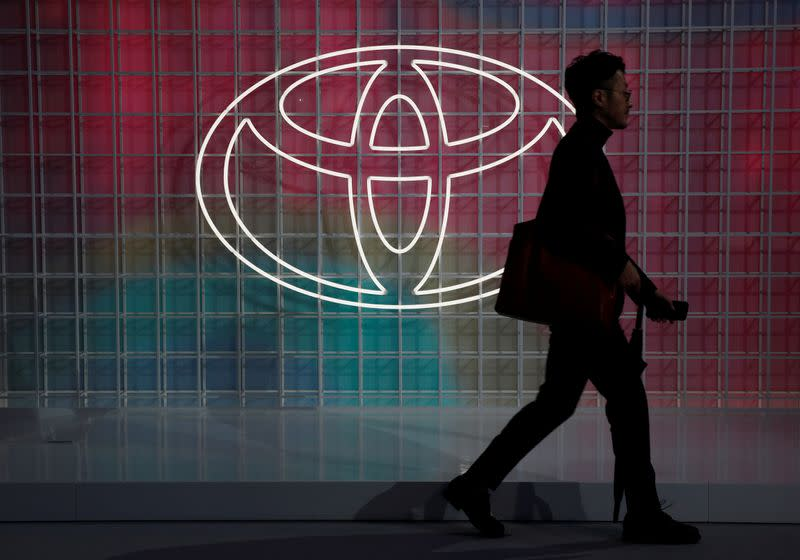 A man walks past a Toyota logo at the Tokyo Motor Show