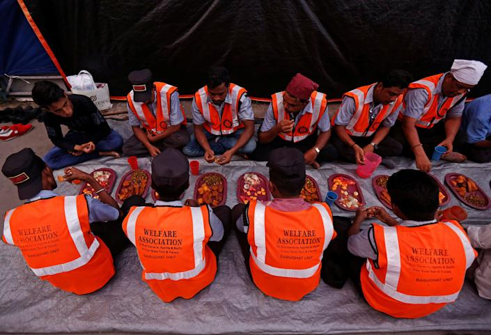 Security guards eat Iftar (breaking fast) meals at a railway platform during the holy fasting month of Ramadan, in Kolkata, India June 14, 2017. REUTERS/Rupak De Chowdhuri
