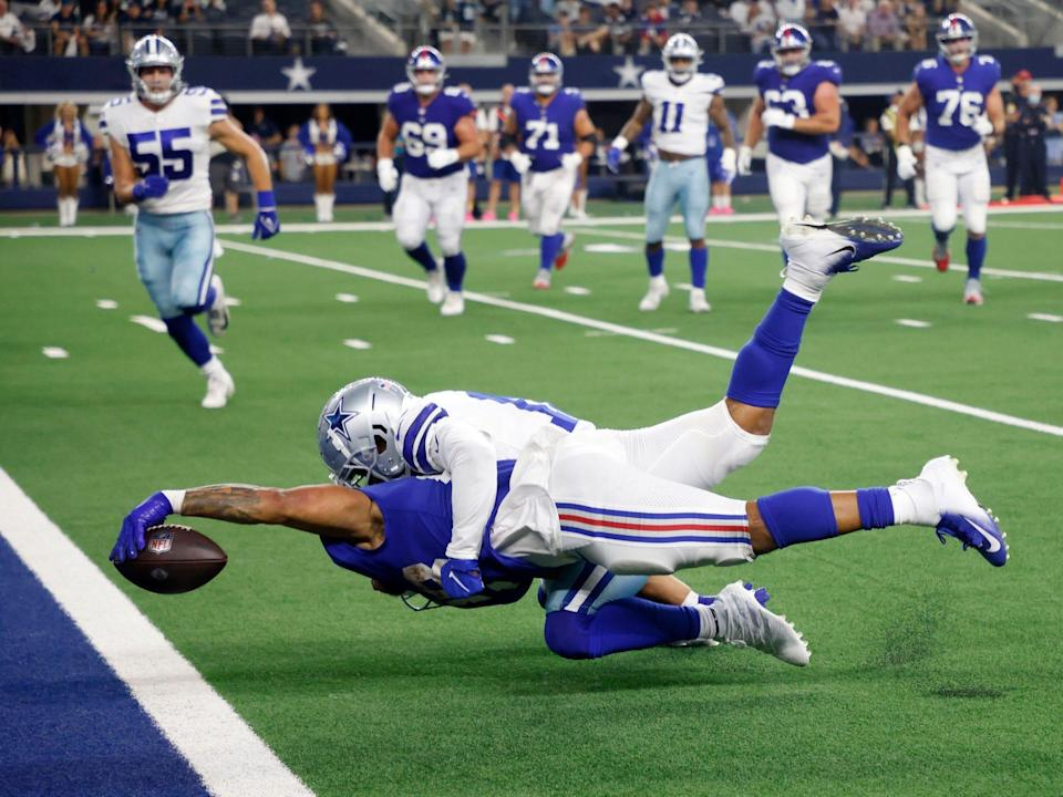 Devontae Booker reaches for the end zone against the Dallas Cowboys.