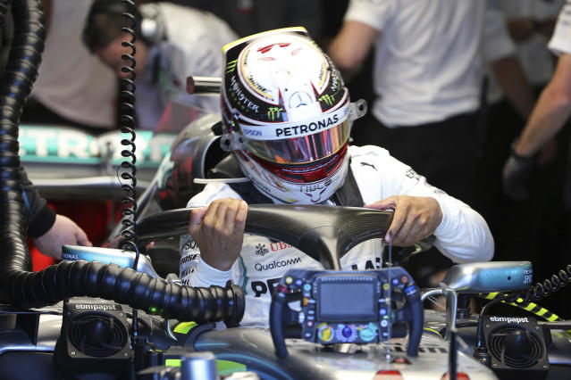 Mercedes driver Lewis Hamilton of Britain struggles to get our of his car at the end of the first practice session at the Australian Formula One Grand Prix in Melbourne, Friday, March 23, 2018. The first race of the 2018 seasons is on Sunday. (AP Photo/Rick Rycroft)
