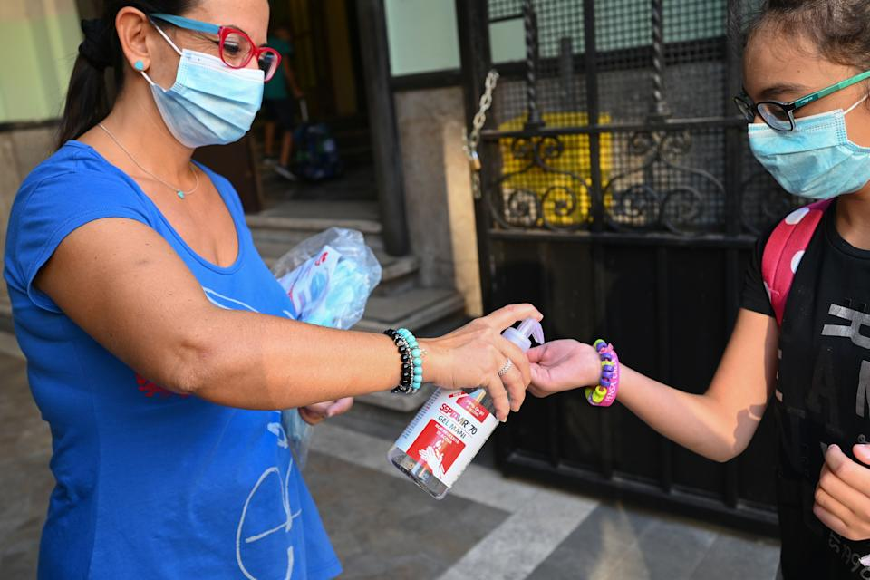 A shool staff (L) wearing a face mask dispenses hand sanitizer gel to a pupil, also wearing a face mask, arriving on September 14, 2020 for the start of the school year at the Luigi Einaudi technical high school in Rome, during the the COVID-19 infection, caused by the novel coronavirus. - Schools in some European nations were set to open on September 14, 2020 with millions returning to classrooms in Italy, Greece and Romania. (Photo by Vincenzo PINTO / AFP) (Photo by VINCENZO PINTO/AFP via Getty Images) (Photo: VINCENZO PINTO via Getty Images)