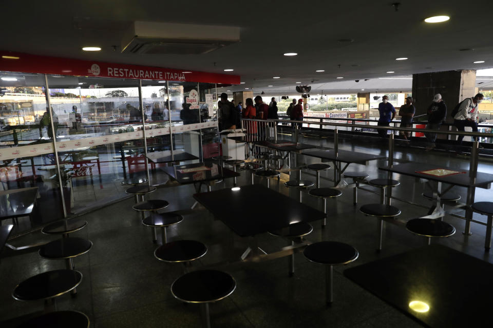 People wait for their orders at a restaurant limited to pick-up on the first day of a two-week-long lockdown to curb the spread of COVID-19 in Brasilia, Brazil, Monday, March 1, 2021. It's the second lockdown since the start of the pandemic one year ago. (AP Photo/Eraldo Peres)