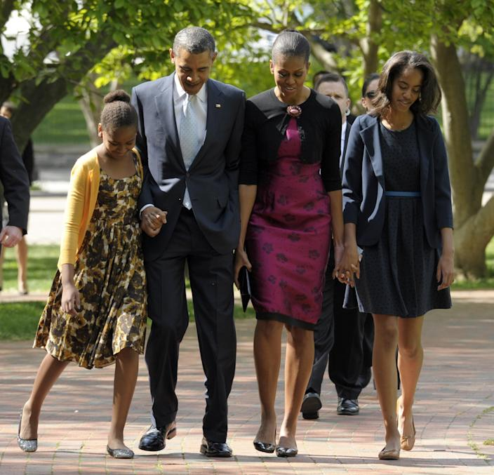 """FILE - In this April 8, 2012, file photo, President Barack Obama, first lady Michelle Obama, daughters Malia, right, and Sasha walk across the square from the White House to St. John's Episcopal Church for Easter service in Washington. Michelle Obama has a new look, both in person and online, and with the president's re-election, she has four more years as first lady, too. The first lady is trying to figure out what comes next for this self-described """"mom in chief"""" who also is a champion of healthier eating, an advocate for military families, a fitness buff and the best-selling author of a book about her White House garden. For certain, she'll press ahead with her well-publicized efforts to reduce childhood obesity and rally the country around its service members. (AP Photo/Susan Walsh, File)"""