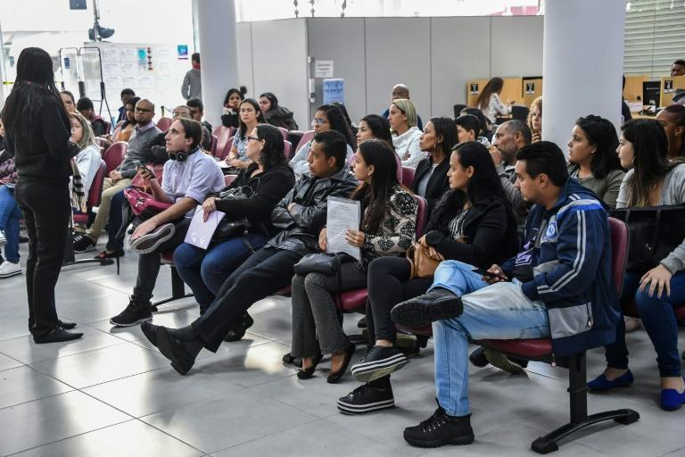 In this file photo taken on June 11, 2019 unemployed people in Brazil wait their turn to get information on job opportunities at the Workers Service Department in Sao Paulo