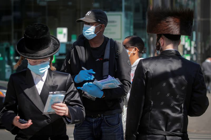 FILE PHOTO: A member of New York City Test and Trace Corp. hands out masks to Ultra-Orthodox Jewish men during the outbreak of coronavirus disease (COVID-19) in the Borough Park section of Brooklyn, New York