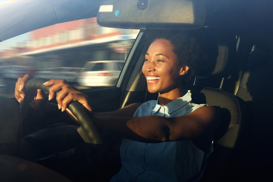 woman smiling while driving in the car, worst things about the suburbs