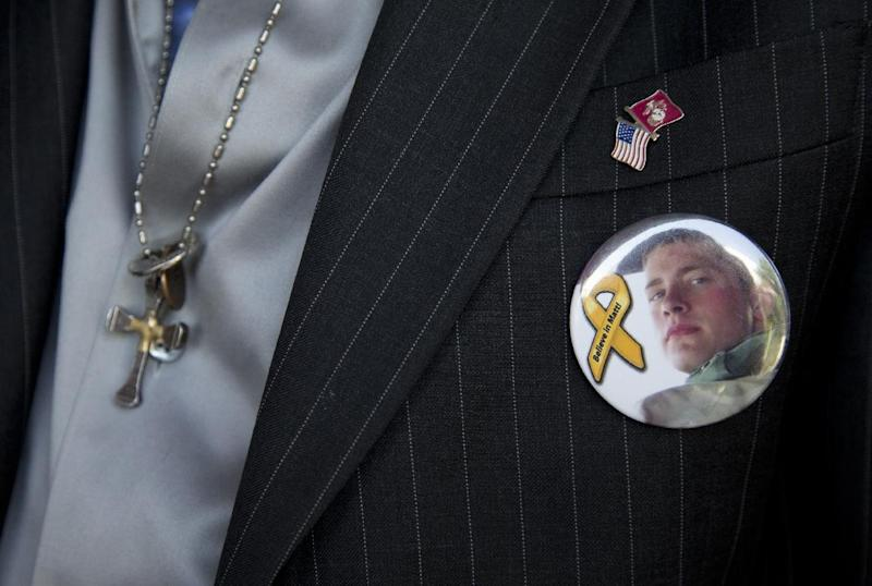 Keith Maupin wears a pin with an image of his son, Sgt. Matt Maupin, in Arlington, Va.,Tuesday, May 13, 2014. A man in Iraqi custody has confessed to killing Sgt. Matt Maupin whose remains were found in 2008. Sgt. Matt Maupin, of Batavia in southwestern Ohio, was captured when insurgents with rocket-propelled grenades and small arms ambushed his fuel convoy near Baghdad on April 9, 2004. (AP Photo)