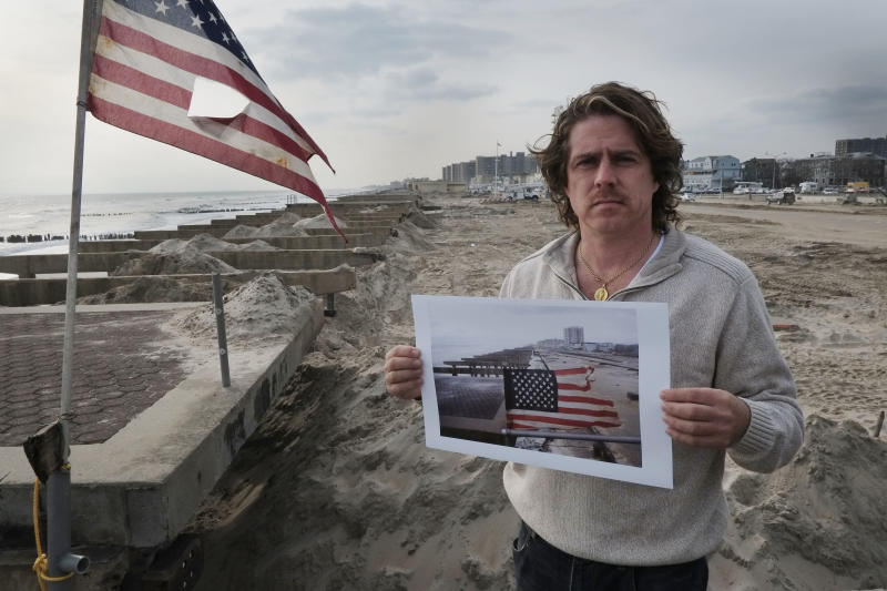 In this photo taken Nov. 18, 2012, Glenn DiResto poses with a photograph he took after Superstorm Sandy, in the Far Rockaway section of the Queens borough of New York. Diresto took the photo the morning after the storm struck the oceanside community and destroyed the boardwalk, left. (AP Photo/Mark Lennihan)