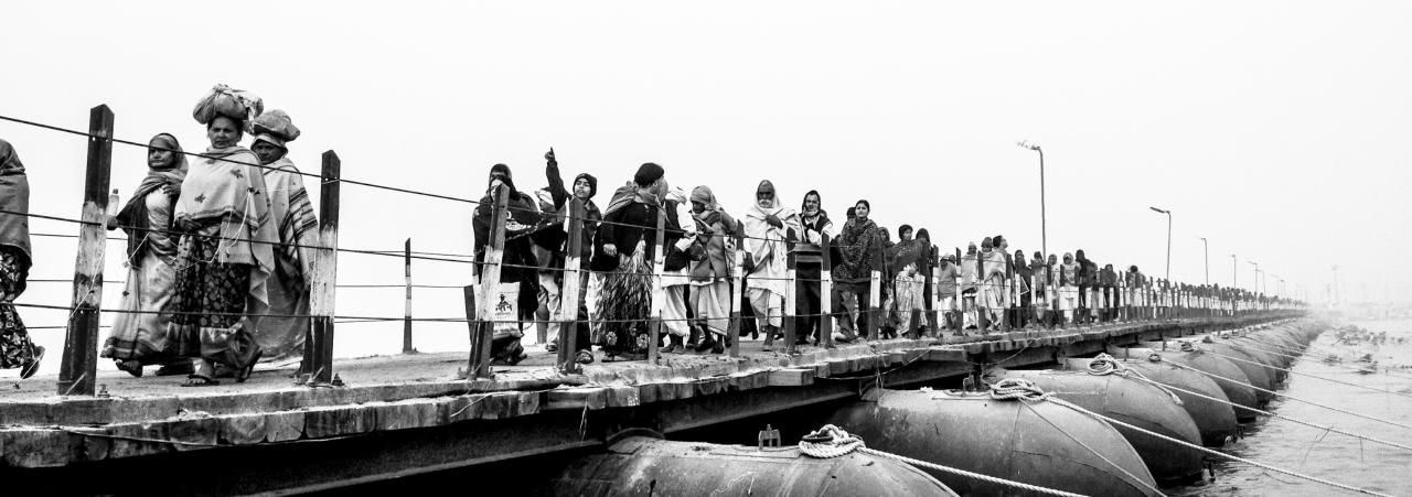 ALLAHABAD, INDIA - FEBRUARY 12: (EDITORS NOTE: Image was created using the iPhone panoramic application) Hindu pilgrims walk across a pontoon bridge from the banks of Sangam, the confluence of the holy rivers Ganges, Yamuna and the mythical Saraswati, during the Maha Kumbh Mela on February 12, 2013 in Allahabad, India. The Maha Kumbh Mela, believed to be the largest religious gathering on earth is held every 12 years on the banks of Sangam, the confluence of the holy rivers Ganga, Yamuna and the mythical Saraswati. The Kumbh Mela alternates between the cities of Nasik, Allahabad, Ujjain and Haridwar every three years. The Maha Kumbh Mela celebrated at the holy site of Sangam in Allahabad, is the largest and holiest, celebrated over 55 days, it is expected to attract over 100 million people. (Photo by Daniel Berehulak/Getty Images)