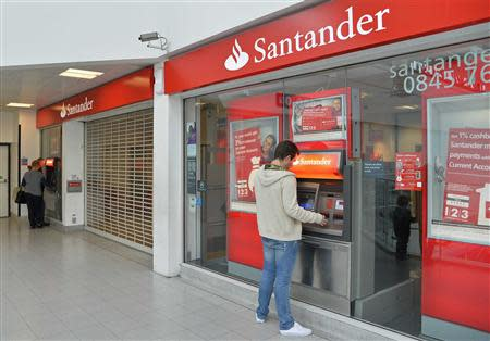 Customers use ATM machines at Surrey Quays branch of Santander Bank, whilst the premises remain closed , in Surrey Quays, south London