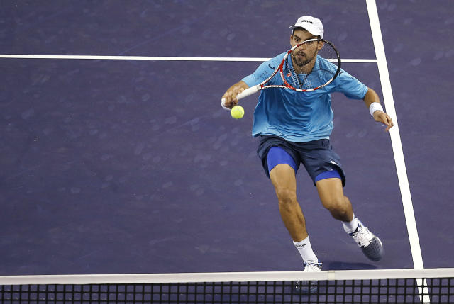 Santiago Giraldo of Colombia returns the ball against John Isner of the United States at the first round of the Shanghai Masters tennis tournament at Qizhong Forest Sports City Tennis Center, in Shanghai, China, Monday, Oct. 7, 2013. Isner won 4-6, 7-5 7-5. (AP Photo/Eugene Hoshiko)