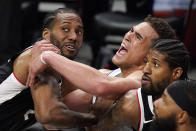 Dallas Mavericks center Dwight Powell, center, tangles with Los Angeles Clippers forward Kawhi Leonard, left, and guard Paul George as they wait for a rebound during the second half in Game 5 of an NBA basketball first-round playoff series Wednesday, June 2, 2021, in Los Angeles. (AP Photo/Mark J. Terrill)