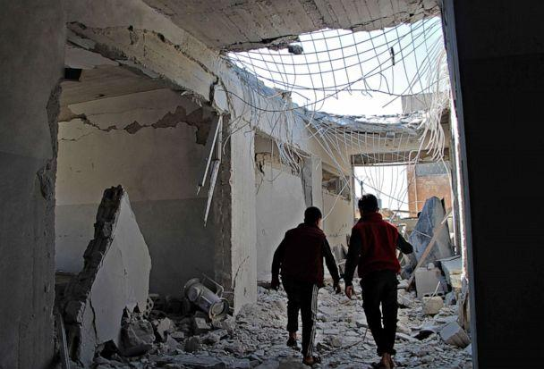 PHOTO: Displaced Syrian children walk through a destroyed school, reportedly targeted in a regime forces' air strike, in northwestern Idlib province on March 3, 2020, near the town of Adwan in Syria. (Ibrahim Yasouf/AFP via Getty Images)