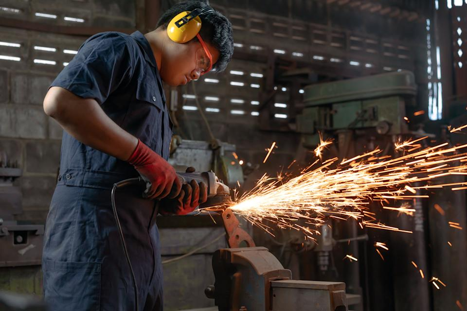 Engineer operating angle grinder hand tools in manufacturing factory. Photo: Getty