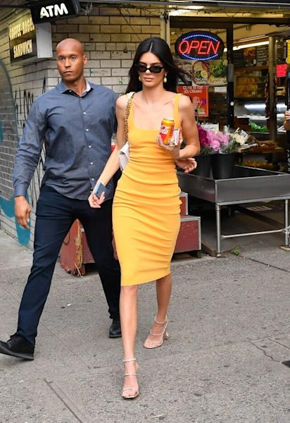 The supermodel looked glamorous at a low-key corner store while picking up a Coca-Cola that coincidentally matched her dress.