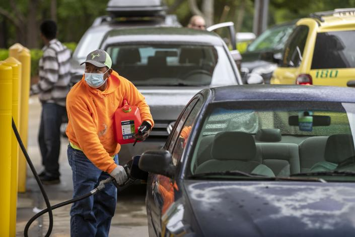 Customers fill up their automobiles and gas containers with fuel at the Circle K on Wednesday, May 12, 2021 in Raleigh, N.C. Several gas stations in the Southeast reported running out of fuel, primarily because of what analysts say is unwarranted panic-buying among drivers, as the shutdown of a major pipeline by hackers entered its fifth day. (Robert Willett/The News & Observer via AP)