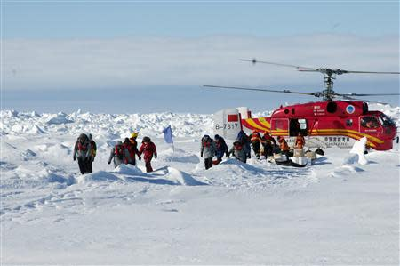 A helicopter from the Xue Long (Snow Dragon) Chinese icebreaker unloads rescued passengers from the ice-bound Russian ship, Akademik Shokalskiy, in East Antarctica, some 100 nautical miles (185 km) east of French Antarctic station Dumont D'Urville and about 1,500 nautical miles (2,800 km) south of Hobart, Tasmania, January 2, 2014, in this handout courtesy of Fairfax's Australian Antarctic Division. REUTERS/Fairfax/Australian Antarctic Division/Handout via Reuters