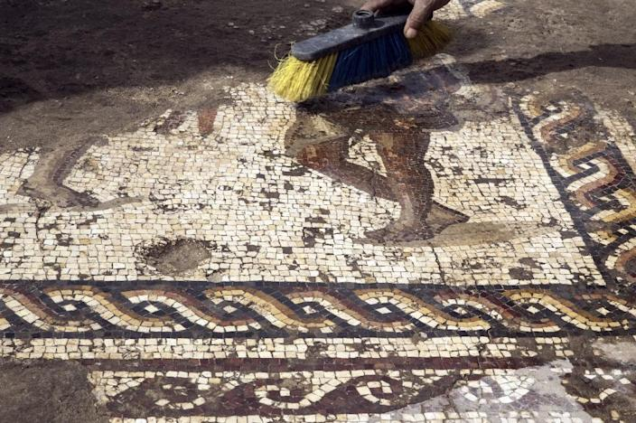 """Workers from the Israeli Antiquity Authority clean a rare Roman-era mosaic on February 8, 2018 north of Tel Aviv which archaeologist Uzi Ad said is of """"high-quality"""" and the kind usually found only in Cyprus and northern Syria (AFP Photo/JACK GUEZ)"""