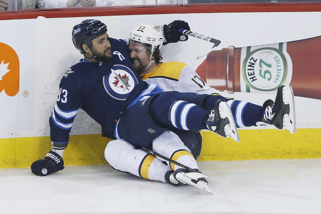 Winnipeg Jets' Dustin Byfuglien (33) checks Nashville Predators' Scott Hartnell (17) during the first period of Game 4 of an NHL hockey second-round playoff series in Winnipeg, Manitoba, Thursday, May 3, 2018. (John Woods/The Canadian Press via AP)