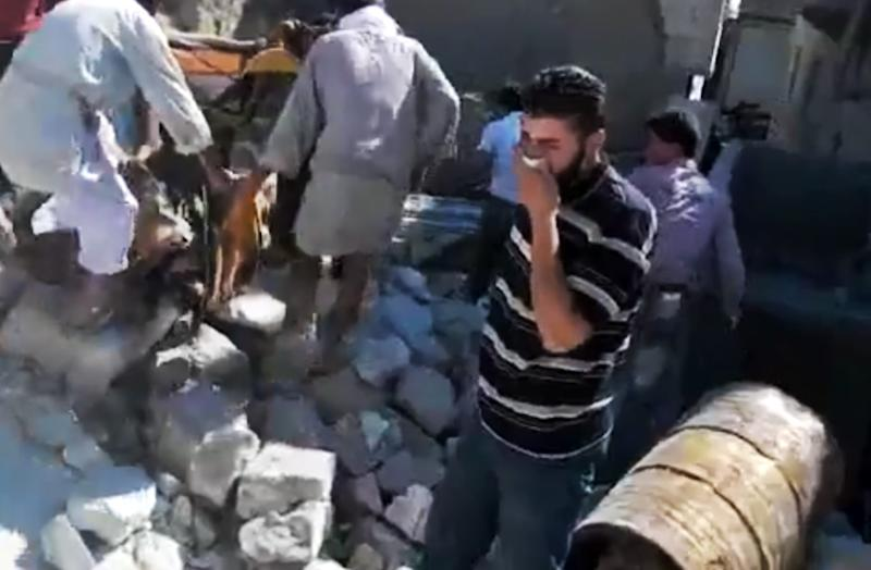 This image made from amateur video released by the Shaam News Network and accessed Sunday, Aug. 12, 2012, purports to show a Syrian man reacting after men, let, lifted a body from the rubble of a destroyed building caused by Syrian forces shelling in Kfarnebel, Idlib province, northern Syria. (AP Photo/Shaam News Network via AP video) THE ASSOCIATED PRESS IS UNABLE TO INDEPENDENTLY VERIFY THE AUTHENTICITY, CONTENT, LOCATION OR DATE OF THIS HANDOUT PHOTO