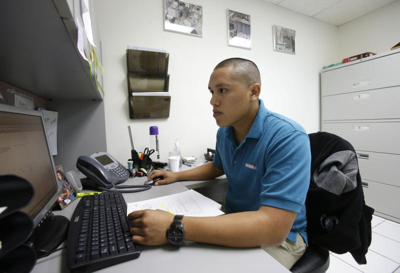 In this Wednesday, June 12, 2013 photo, Jorge Tume is shown working on a computer at a concrete company in Miami. Tume's parents brought him and his younger brother to the U.S. from Peru on tourist visas when they were young and decided to stay, becoming unauthorized immigrants with no legal status. Now, one year after President Barack Obama announced an executive order allowing young people living in the U.S. illegally to stay and work, nearly 300,000 young adults previously living illegally in the United States have been granted permission to stay and work through the program, the most significant shift in immigration policy in recent decades. (AP Photo/Wilfredo Lee)