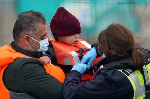 A young boy is helped by a Border Force officer in Dover