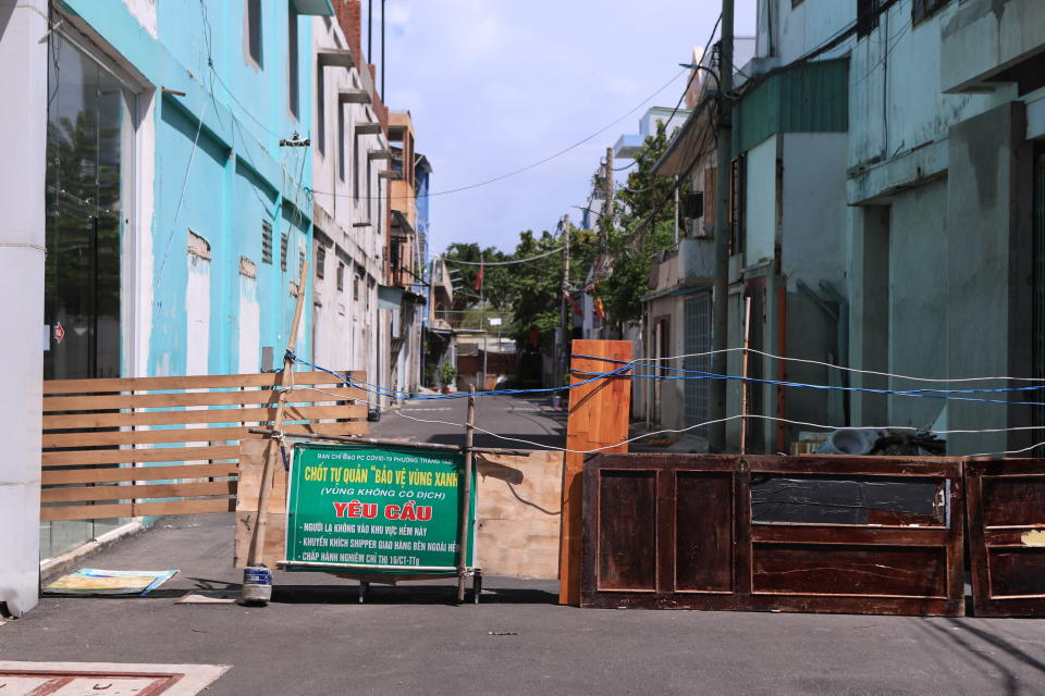 An alley is barricaded with door panels in Vung Tau, Vietnam, Monday, Sept. 20, 2021. In Vung Tau, just outside Ho Chi Minh city, streets are sealed and checkpoints are set up to control the movement of people. Barbed wire, door panels, steel sheets, chairs and tables are among materials being used to fence up alleys and isolate neighborhoods.(AP Photo/Hau Dinh)