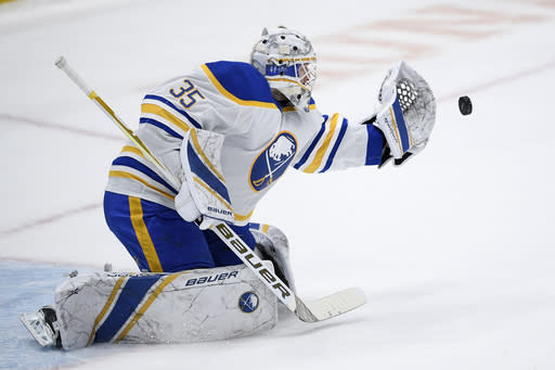 Buffalo Sabres goaltender Linus Ullmark (35) reaches for the puck during a shootout of an NHL hockey game against the Washington Capitals, Sunday, Jan. 24, 2021, in Washington. (AP Photo/Nick Wass)