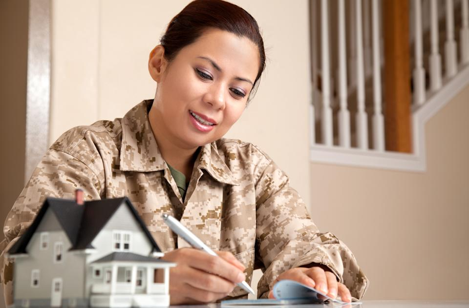 US Marine Female Soldier at Home with Real Estate Paperwork.