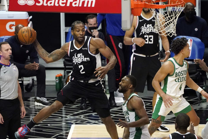 Los Angeles Clippers forward Kawhi Leonard (2) passes the ball next to Boston Celtics guard Kemba Walker, center, during the second half of an NBA basketball game Friday, Feb. 5, 2021, in Los Angeles. (AP Photo/Marcio Jose Sanchez)
