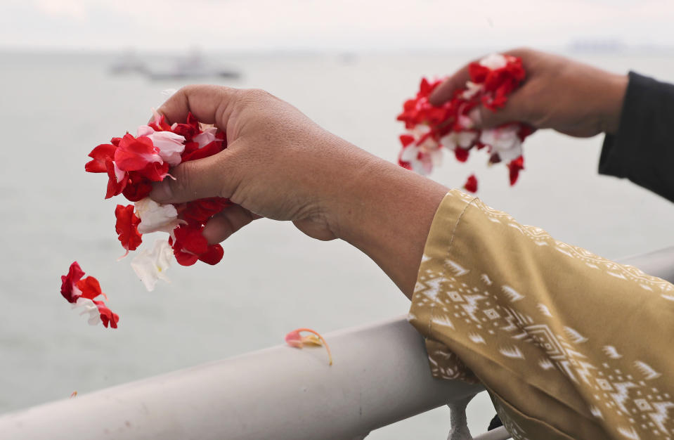Relatives sprinkle flowers into the Java Sea where Sriwijaya Air flight SJ-182 crashed on Jan. 9 killing all of its passengers, during a memorial ceremony held on deck of Indonesian Navy Ship KRI Semarang, near Jakarta in Indonesia, Friday, Jan. 22, 2021. (AP Photo/Tatan Syuflana)