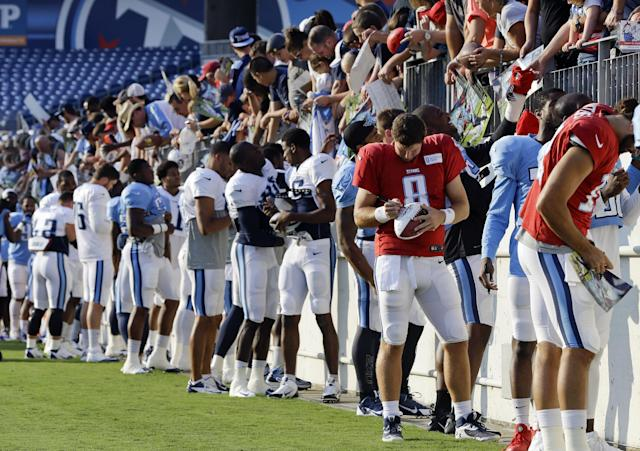 Tennessee Titans players sign autographs before an NFL football training camp practice in LP Field on Saturday, Aug. 2, 2014, in Nashville, Tenn. (AP Photo/Mark Humphrey)
