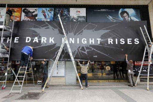 Employees remove promotional boards from the cinema where the French premiere of the Batman movie was to take place