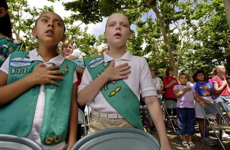 FILE - In this Monday, June 14, 2004 file photo, Santa Clara County Girl Scouts of America members Viris Rios, 10, left, and Madeline Hurst, 10, center, recite the Pledge of Allegiance during the 20th Annual Flag Day Ceremony at the Santa Clara County Government Center in San Jose, Calif. It's been 100 years since Juliette Gordon Low recruited the first scouts in Georgia. Low's original registration book from March of 1912 shows 102 recruits. Now there are 2.3 million active Girl Scouts nationwide. (AP Photo/Paul Sakuma, File)