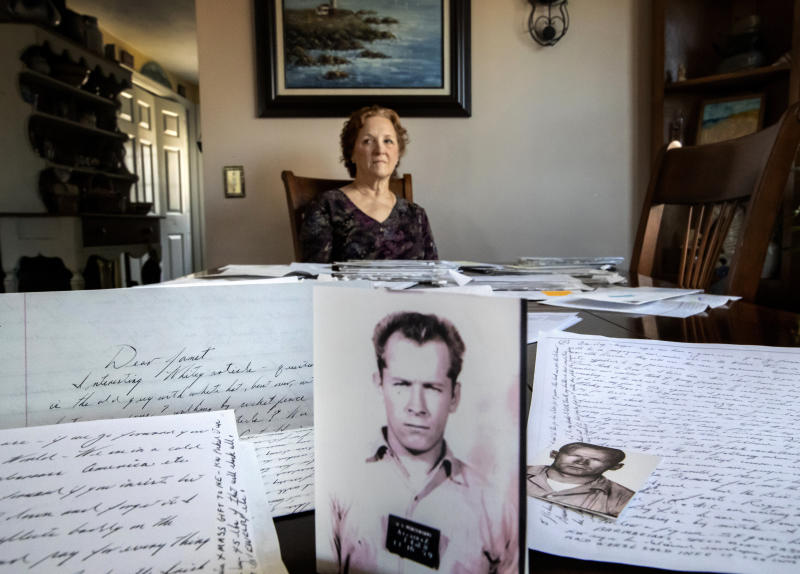 """Janet Uhlar sits for a photo at her dining room table with an arrangement of letters and pictures she received through her correspondence with imprisoned Boston organized crime boss James """"Whitey"""" Bulger, Friday, Jan. 31, 2020, in Eastham, Mass. Uhlar was one of 12 jurors who found Bulger guilty in a massive racketeering case, including involvement in 11 murders. But now she says she regrets voting to convict Bulger on the murder charges, because she learned he was an unwitting participant in a secret CIA experiment in which he was dosed with LSD on a regular basis for 15 months. (AP Photo/David Goldman)"""