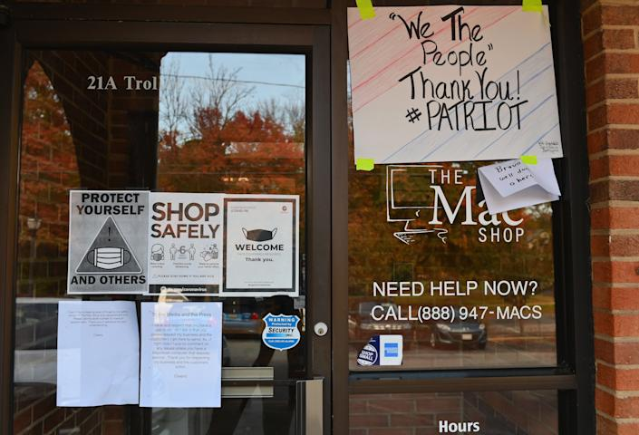 Signs of support are posted on the windows and door of the Mac Shop in Wilmington, Del.