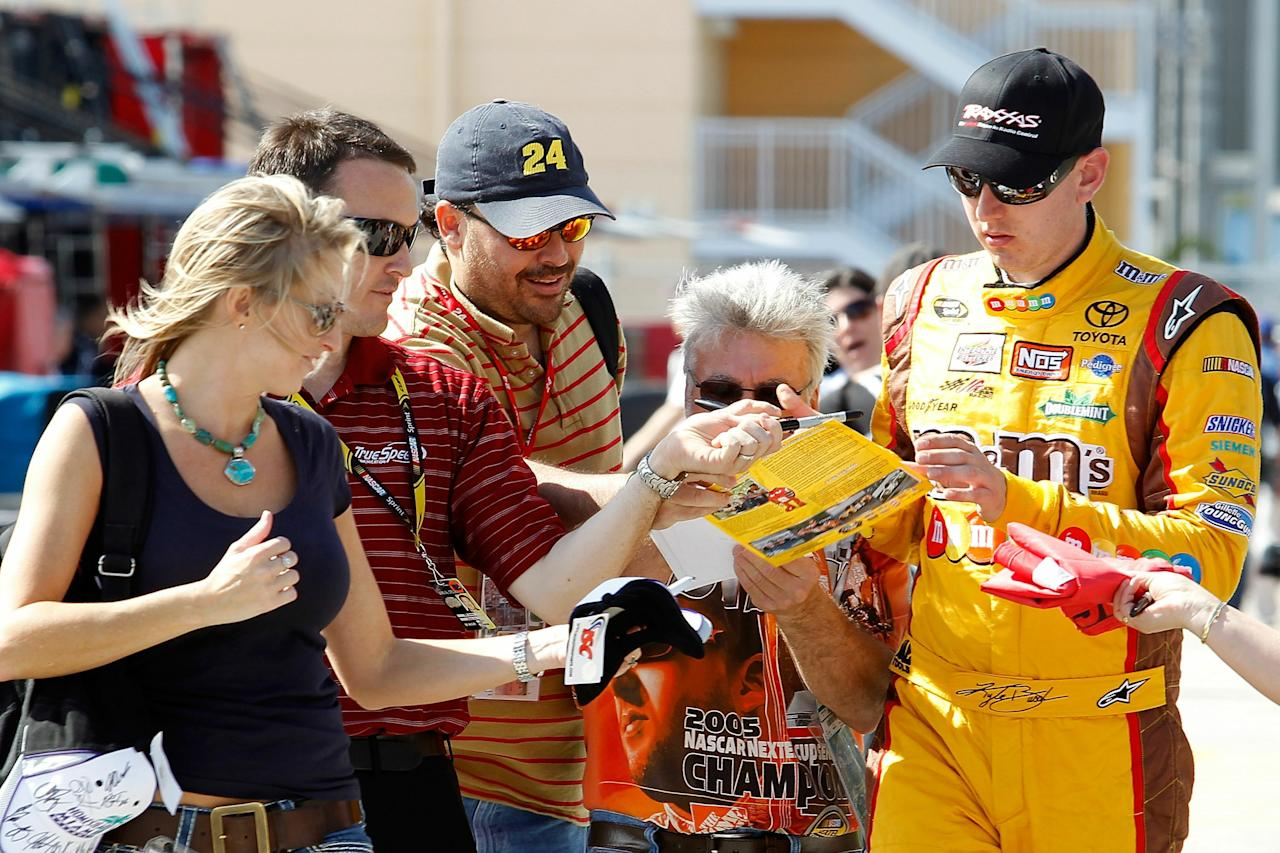 HOMESTEAD, FL - NOVEMBER 19:  Kyle Busch, driver of the #18 M&M'sToyota, signs autographs for fans during practice for the NASCAR Sprint Cup Series Ford 400 at Homestead-Miami Speedway on November 19, 2010 in Homestead, Florida.  (Photo by Todd Warshaw/Getty Images for NASCAR)
