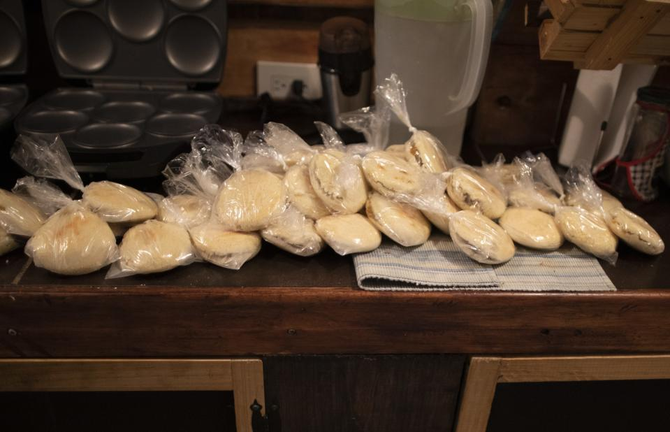 Arepas or corn flour patties made by Andres Burgos, a 55-year-old publicist, that he will distribute to the needy, sit on a kitchen counter in his home in Caracas, Venezuela, Wednesday, Oct. 21, 2020. In March, after authorities imposed stiff quarantine measures to combat the new coronavirus, the number of homeless and even well-dressed people he saw digging through garbage increased. That's when he went from handing out 20 arepas a day to 150. (AP Photo/Ariana Cubillos)