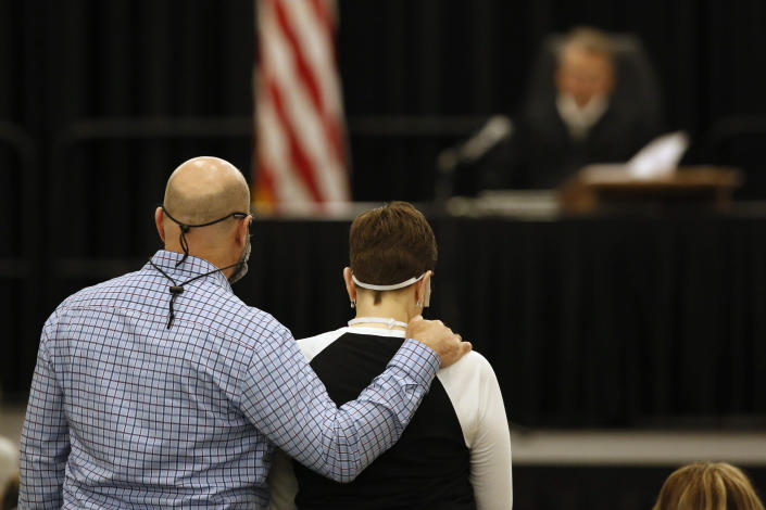 Dave Domingo, left, and his sister, Debbi Domingo McMullan, listen as Joseph James DeAngelo is charged with the 1981 murder of their mother, Cheri Domingo, in Sacramento Superior Court in Sacramento, Calif., Monday, June 29, 2020. DeAngelo, 74, accused of being the Golden State Killer, pleaded guilty to the murder of Cheri Domingo and 12 other victims 40 years ago during a sadistic series of assaults and slayings in California. Due to the large numbers of people attending, the hearing was held at a ballroom at California State University, Sacramento to allow for social distancing. (AP Photo/Rich Pedroncelli)
