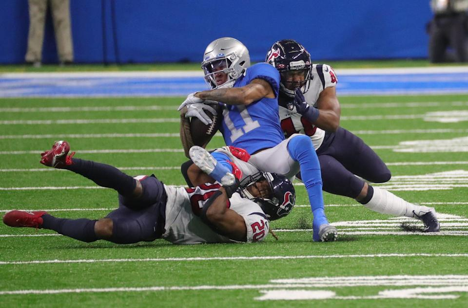 Lions wide receiver Marvin Jones makes a catch against Texans strong safety Justin Reid, left, and linebacker Nate Hall during the second half of the Lions' 41-25 loss at Ford Field Thursday, Nov. 26, 2020.
