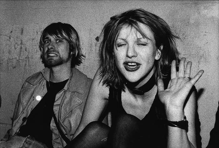 Black-and-white photo of Kurt and Courtney sitting against a wall