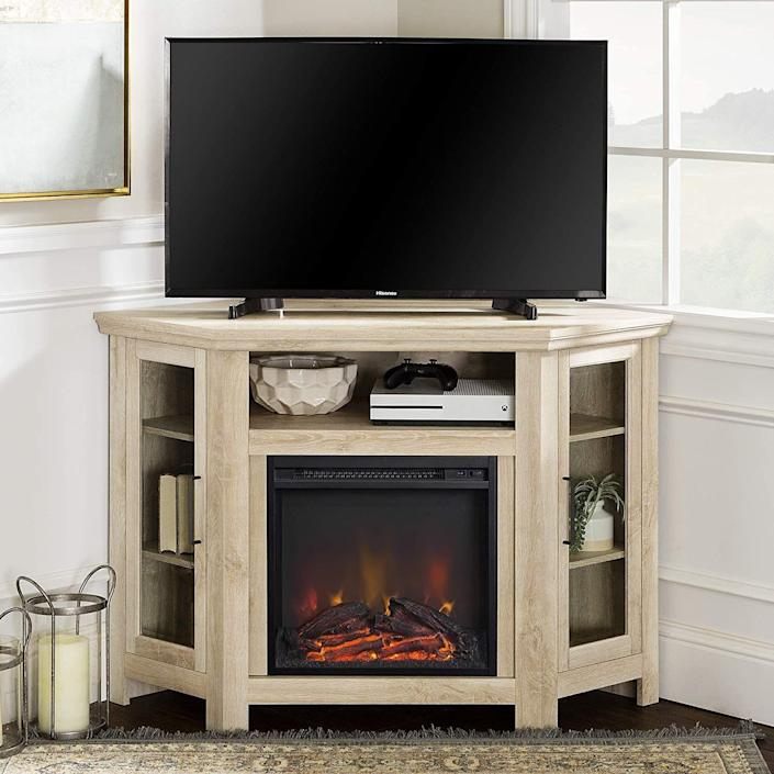 """<p><strong>Walker Edison</strong></p><p>amazon.com</p><p><strong>$271.95</strong></p><p><a href=""""https://www.amazon.com/WE-Furniture-Corner-Fireplace-Console/dp/B071RNDH3H/?tag=syn-yahoo-20&ascsubtag=%5Bartid%7C10060.g.37621995%5Bsrc%7Cyahoo-us"""" rel=""""nofollow noopener"""" target=""""_blank"""" data-ylk=""""slk:Shop Now"""" class=""""link rapid-noclick-resp"""">Shop Now</a></p><p><strong>Key Specs</strong></p><ul><li><strong>Dimensions</strong>: 32 x 20 x 47.2 inches </li><li><strong>Main material</strong>: Manufactured wood</li><li><strong>Weight capacity</strong>: 100 pounds</li><li><strong>Max TV screen size: </strong>55 inches</li><li><strong>Adjustable shelves</strong>: Yes </li></ul><p>For those who are tight on space—or don't want the TV to be the family room's main attraction—a corner console is a smart choice. This charming fireplace TV stand supports screens up to 55 inches and features two adjustable shelves on each side behind tempered-glass doors, perfect for displaying photos, books, or ceramics. There's also a wide-open shelf for stashing gaming equipment or a soundbar. </p><p>The fireplace emits 4,600 BTUs of heat, enough to warm a room up to roughly 400 square feet, and the console comes in a handful of other neutral finishes, including espresso, gray, and a traditional brown, but there's no remote control. </p>"""