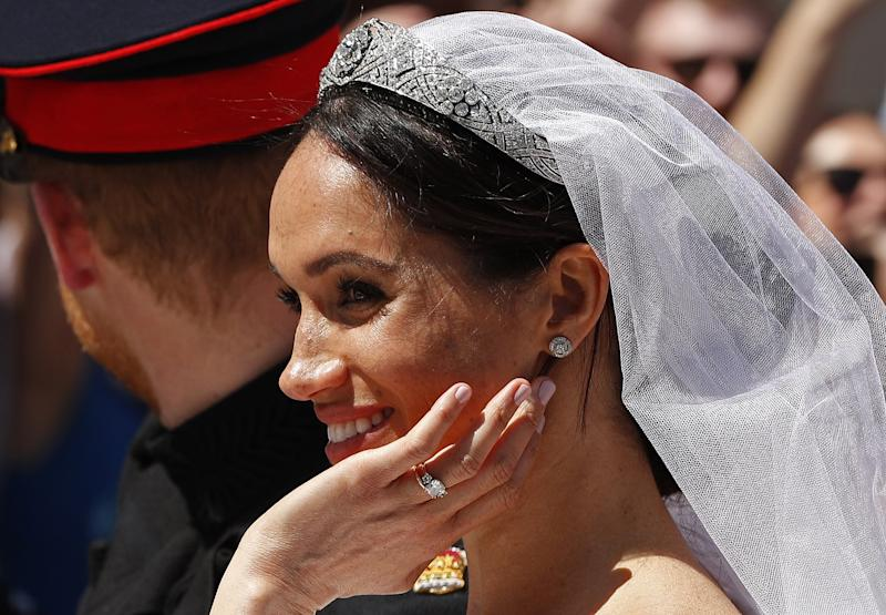 Meghan, Duchess of Sussex reacts from the Ascot Landau Carriage during the carriage procession with Britain's Prince Harry, Duke of Sussex on the High Street in Windsor, on May 19, 2018 after their wedding ceremony. (Photo by JOHN SIBLEY / POOL / AFP) (Photo credit should read JOHN SIBLEY/AFP/Getty Images)