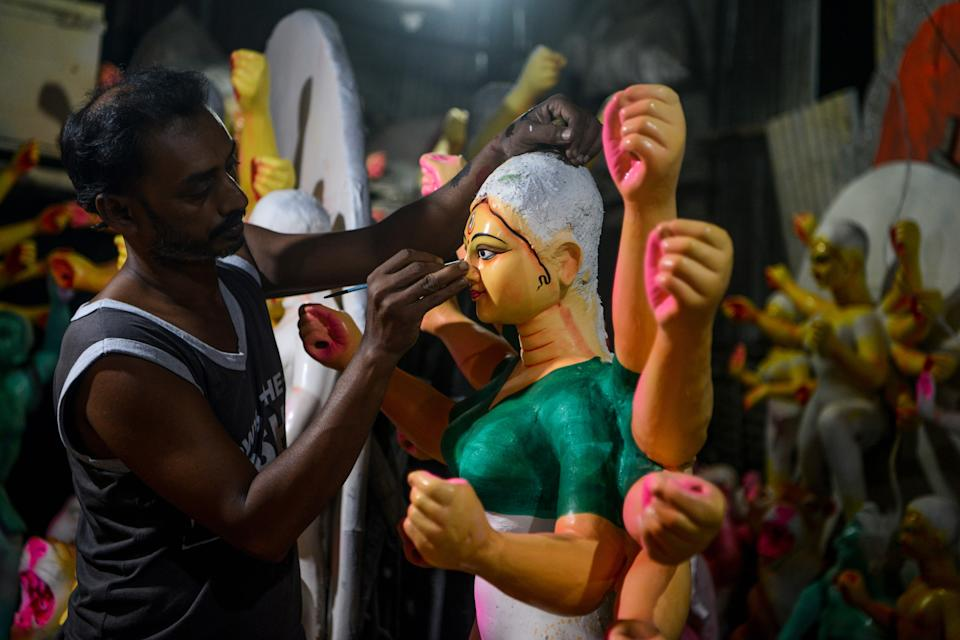 An artisan works on clay sculptures depicting Hindu goddess Durga at a workshop, ahead of the upcoming 'Durga Puja' festival, in Siliguri on October 9, 2020. (Photo by Diptendu DUTTA / AFP) (Photo by DIPTENDU DUTTA/AFP via Getty Images)