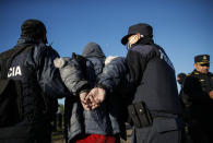A man is detained by police during the eviction of a squatters camp in Guernica, Buenos Aires province, Argentina, Thursday, Oct. 29, 2020. A court ordered the eviction of families who have been squatting at the camp since July, but the families say they have nowhere to go amid the COVID-19 pandemic. (AP Photo/Natacha Pisarenko)