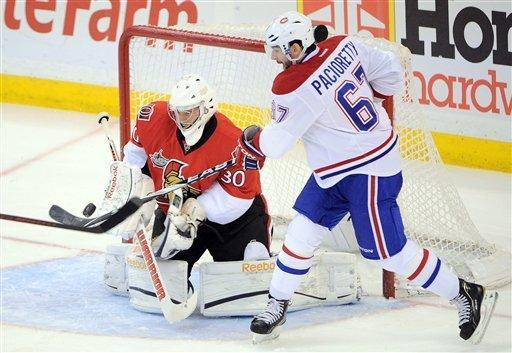 CORRECTS YEAR - Ottawa Senators' Ben Bishop, left, makes a save against Montreal Canadiens' Max Pacioretty during first period NHL hockey action at the Scotiabank Place in Ottawa, Ontario, on Friday, March 16, 2012. (AP Photo/The Canadian Press, Sean Kilpatrick)