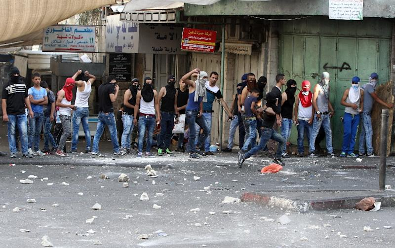 Palestinian youths stand in line as they throw stones towards Israeli security forces during clashes in the West Bank town of Hebron on October 4, 2015 (AFP Photo/Hazem Bader)